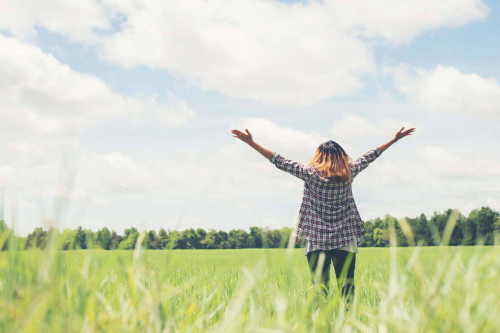 Freedom Young beautiful woman stretching her arms into the sky enjoy and happy with fresh air at grassland.